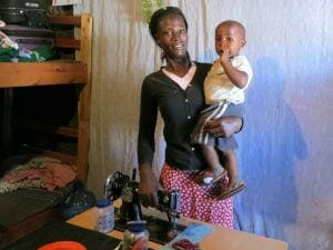 Lillian with her son Ray and the sewing machine she bought with her loan!